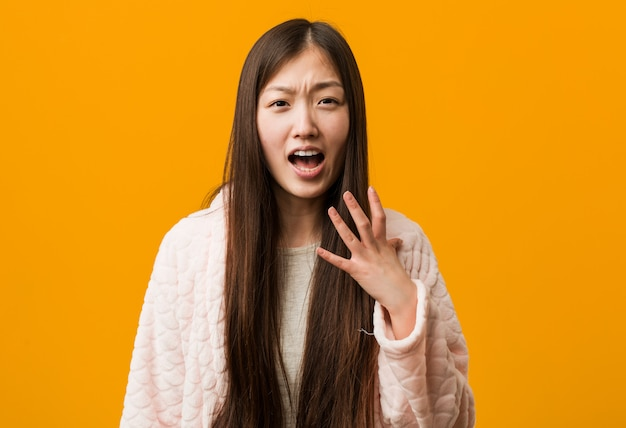 Young chinese woman in pajama screaming with rage.
