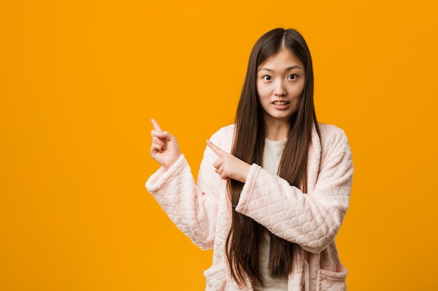Young chinese woman in pajama shocked pointing with index fingers to a copy space.