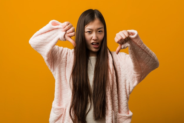 Young chinese woman in pajama showing thumb down and expressing dislike.