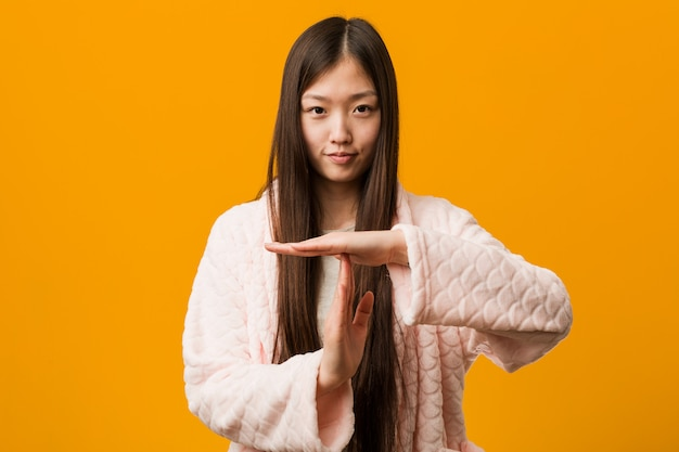 Young chinese woman in pajama showing a timeout gesture