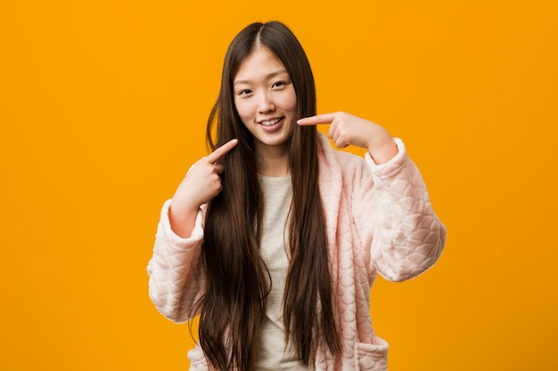 Young chinese woman in pajama smiles, pointing fingers at mouth.