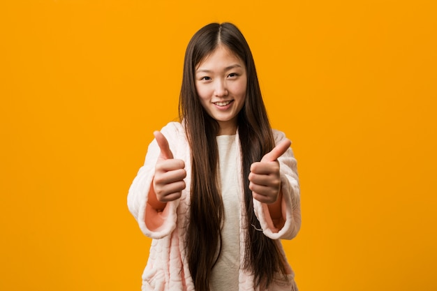 Young chinese woman in pajama with thumbs ups, cheers about something, support and respect concept.