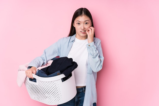 Young chinese woman picking up dirty clothes isolated biting fingernails, nervous and very anxious.