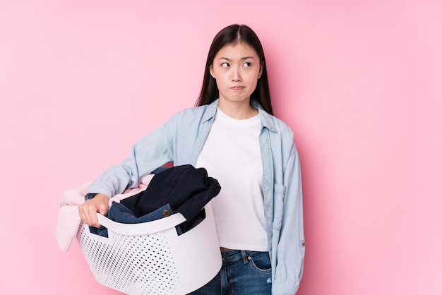 Young chinese woman picking up dirty clothes isolated confused, feels doubtful and unsure.