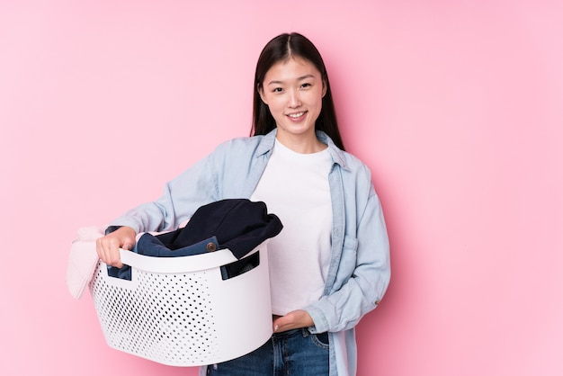 Young chinese woman picking up dirty clothes isolated happy, smiling and cheerful.