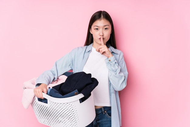 Young chinese woman picking up dirty clothes isolated keeping a secret or asking for silence.