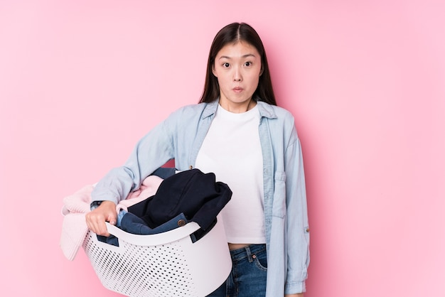 Young chinese woman picking up dirty clothes isolated shrugs shoulders and open eyes confused.