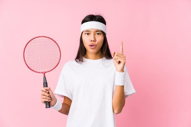 Молодая китаянка играет в бадминтон в розовой стене, имея отличную идею, концепцию творчества.