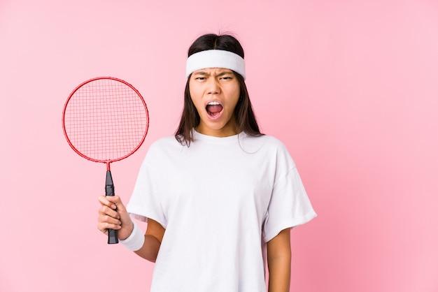Молодая китайская женщина играет в бадминтон в розовой стене кричать очень злой и агрессивный.