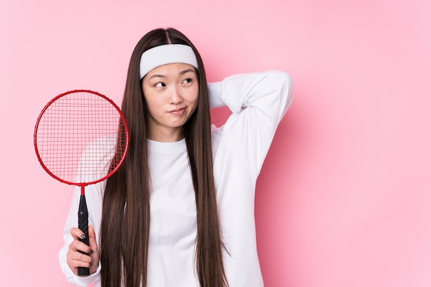 Young chinese woman playing badminton isolated touching back of head, thinking and making a choice.