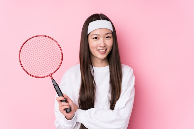 Young chinese woman playing badminton laughing and having fun.
