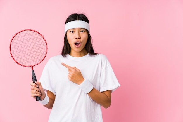 Young chinese woman playing badminton in a pink background pointing to the side