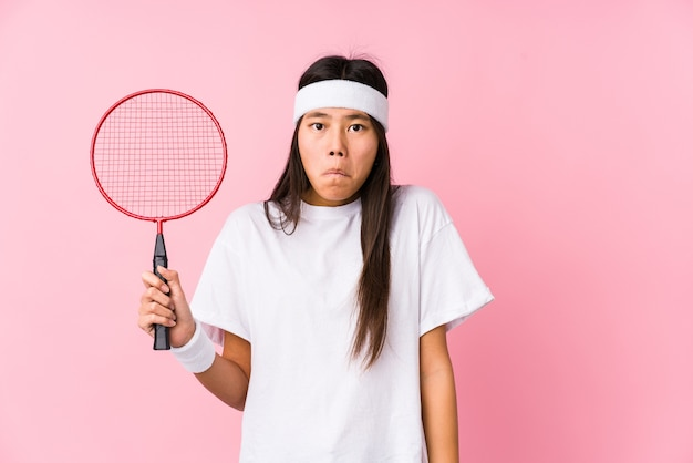 Young chinese woman playing badminton on pink background shrugs shoulders and open eyes confused.