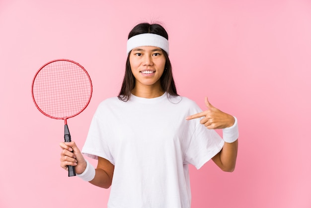 Young chinese woman playing badminton in a pink wall person pointing by hand to a shirt copy space, proud and confident
