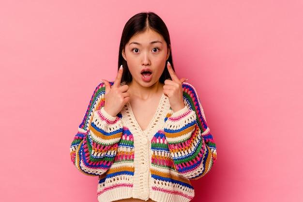 Молодая китаянка, указывая вверх с открытым ртом.