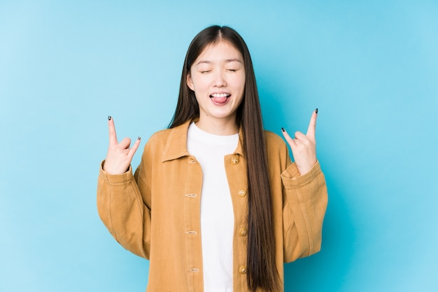 Young chinese woman posing in a blue background isolated showing rock gesture with fingers