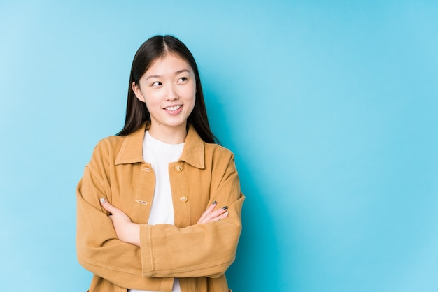 Young chinese woman posing in a blue background isolated smiling confident with crossed arms.