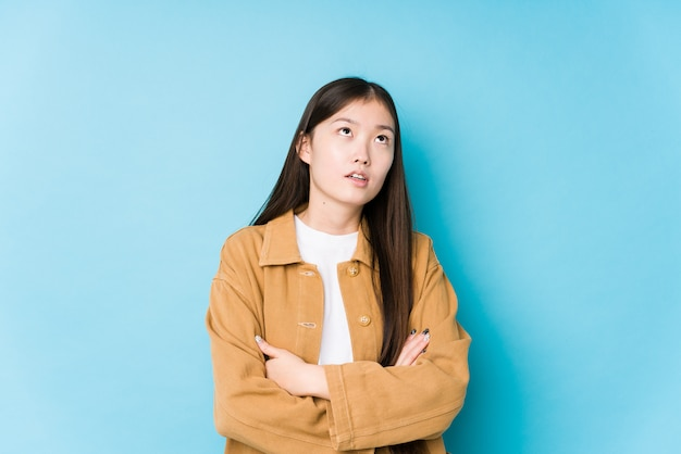 Young chinese woman posing in a blue wall tired of a repetitive task.