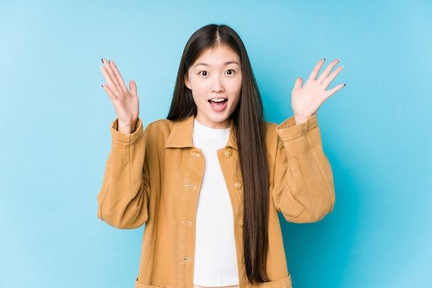 파란색 배경에서 포즈 젊은 중국 여자는 즐거운 놀라움을 받고, 흥분하고 손을 올리는 격리.