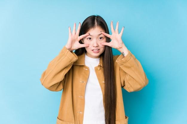 Молодая китаянка позирует в синей изолированной поверхности, держа глаза открытыми, чтобы найти возможность успеха.