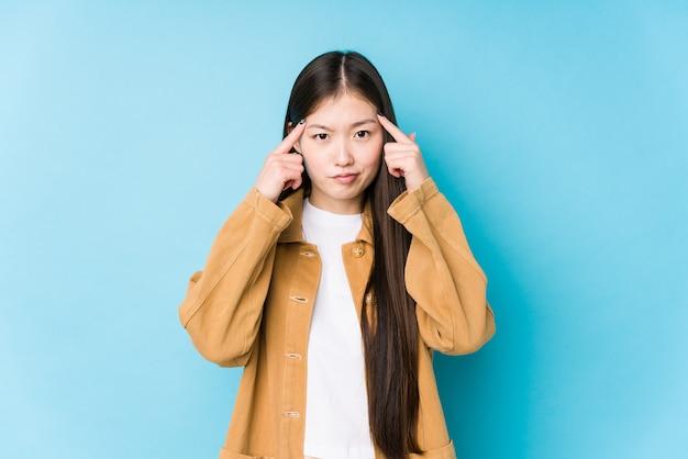 Молодая китаянка позирует у синей стены изолированно сосредоточилась на задаче, держа указательные пальцы указывая головой.