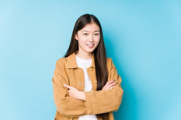Молодая китаянка позирует в синей стене изолирована, которая чувствует себя уверенно и решительно скрещивает руки.