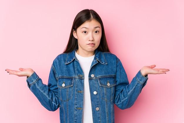 ピンクの背景でポーズをとっている若い中国人女性は、コピースペースを保持するために混乱して疑わしい肩をすくめる肩を孤立させました。