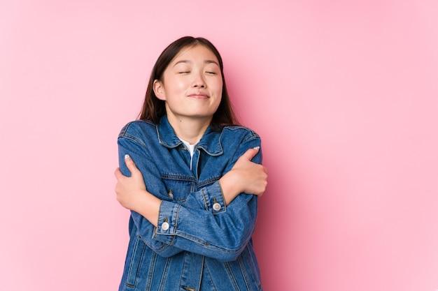 Молодая китаянка позирует в розовом фоне, изолированные объятия, улыбаясь беззаботно и счастливо.