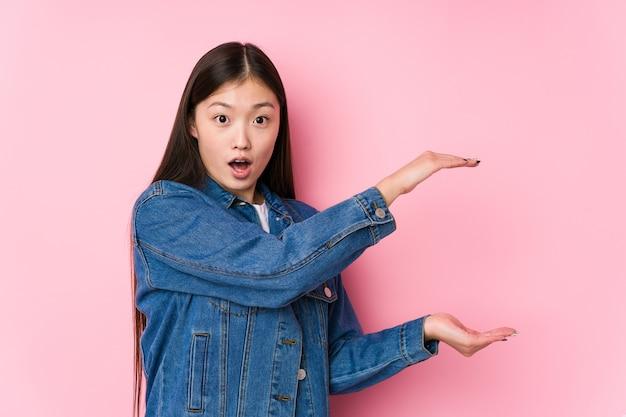 분홍색 배경에서 포즈를 취하는 젊은 중국 여자는 충격과 손 사이의 복사 공간을 잡고 놀랐습니다.