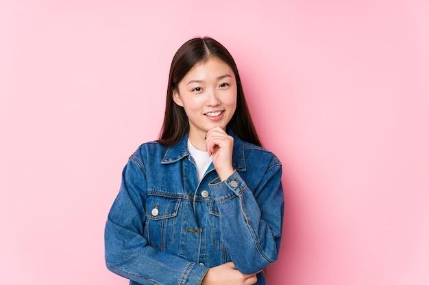 Молодая китаянка позирует в розовом фоне изолированной улыбающейся счастливой и уверенной, трогающей подбородок рукой.