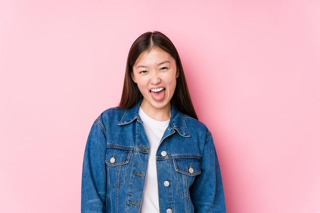Молодая китайская женщина представляя в розовой стене изолировала смешной и дружелюбный вставлять вне язык.