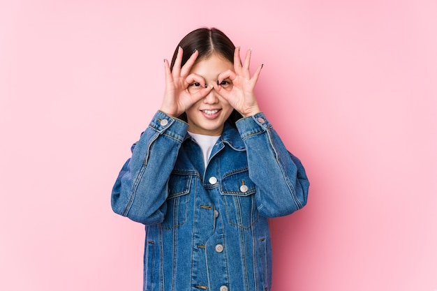 Молодая китаянка позирует в розовой стене изолированы, показывая знак хорошо над глазами