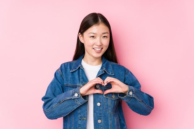 Молодая китайская женщина представляя в розовой стене изолировала усмехаться и показывать форму сердца с руками.
