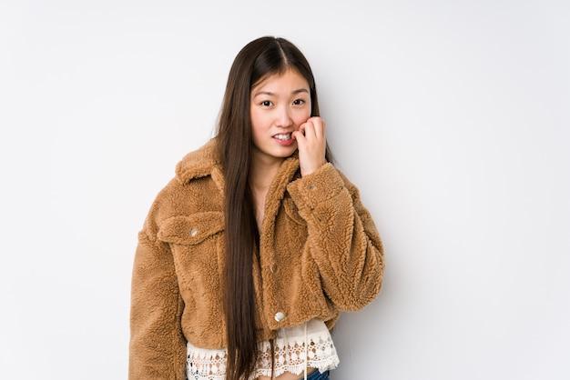Молодая китайская женщина представляя в белой предпосылке изолировала сдерживая ногти, нервный и очень тревоженый.