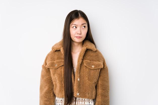 흰색으로 포즈를 취하는 젊은 중국 여성은 혼란스럽고 의심스럽고 확신이 없습니다.