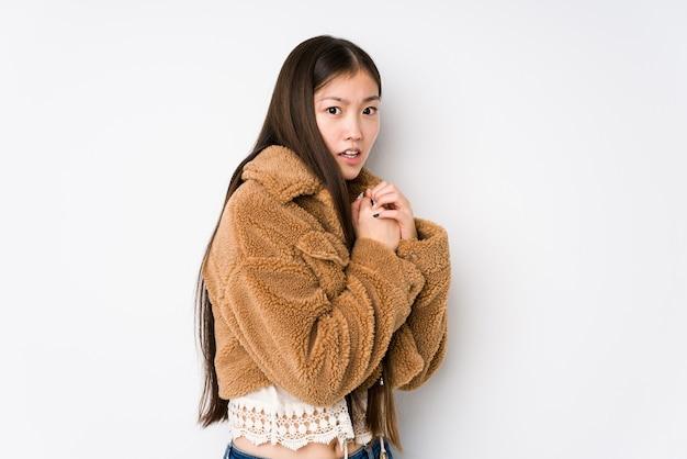 Молодая китаянка позирует в белом изолированном испуганном и напуганном.