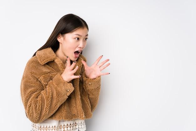 Молодая китаянка, позирующая в изолированной белой стене, громко кричит, держит глаза открытыми, а руки напряженными.