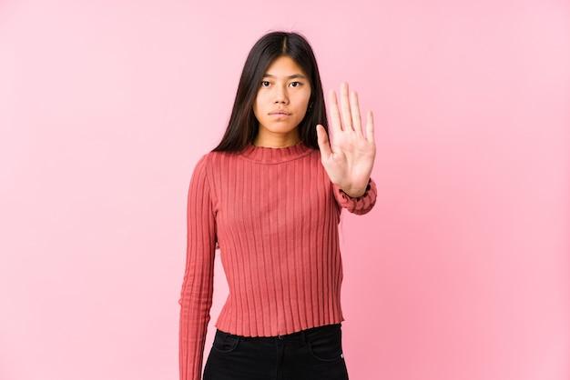 Молодая китаянка позирует изолированным стоя с протянутой рукой, показывая знак остановки, предотвращая вас.