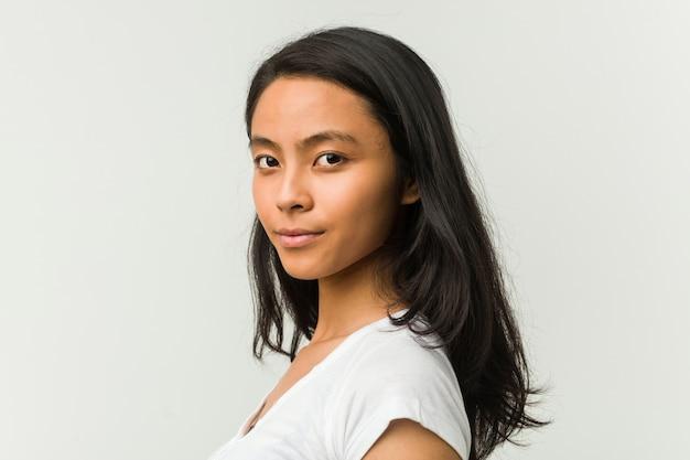 Молодая китайская женщина позирует на белой стене