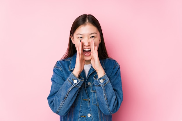Young chinese woman posing on pink isolated shouting excited to front.