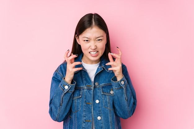 Young chinese woman posing in a pink  isolated upset screaming with tense hands.