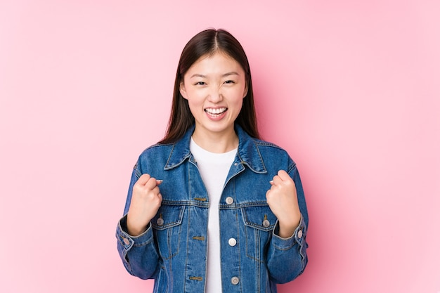 Young chinese woman posing in a pink surface isolated cheering carefree and excited. victory concept.