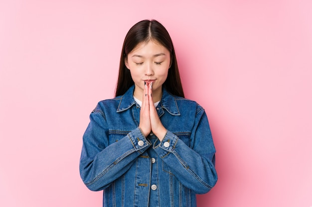 Young chinese woman posing in a pink wall isolated holding hands in pray near mouth, feels confident.