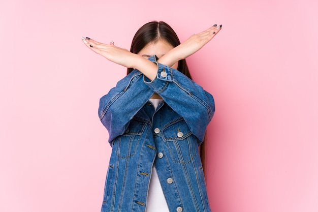 Young chinese woman posing in a pink wall isolated keeping two arms crossed, denial concept.