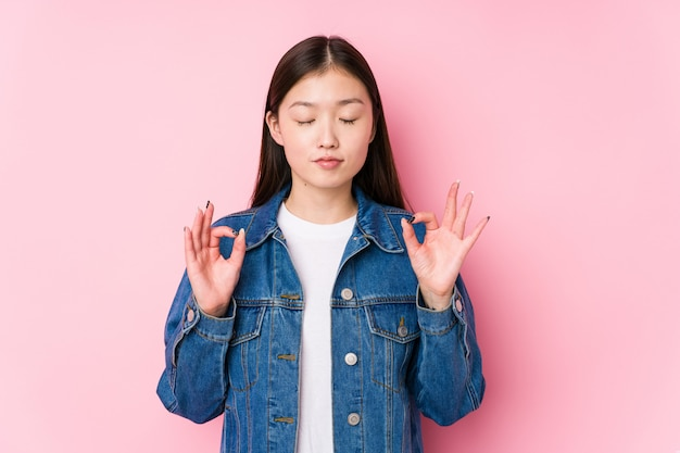 Young chinese woman posing in a pink wall relaxes after hard working day performing yoga.