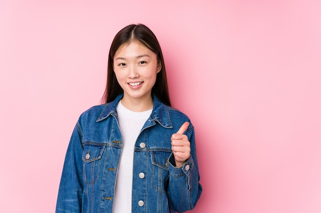 Young chinese woman posing in a pink wall smiling and raising thumb up
