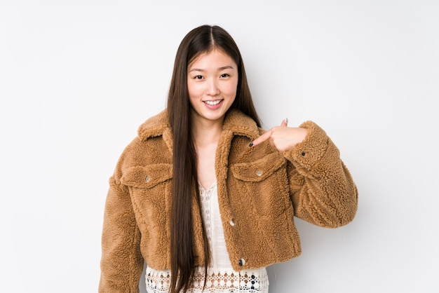 Young chinese woman posing in a white background isolated person pointing by hand to a shirt copy space, proud and confident