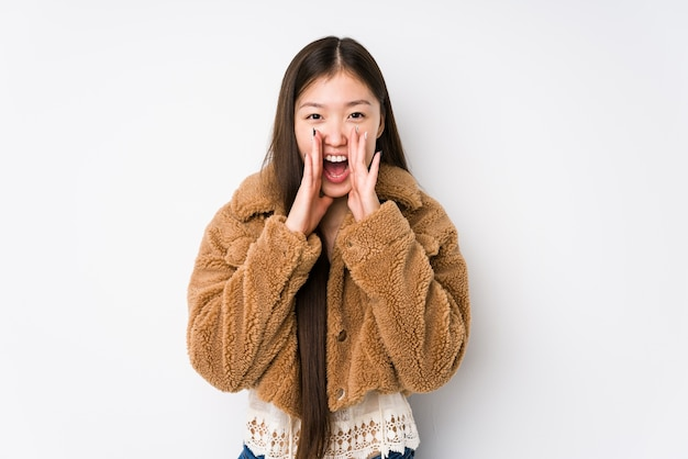 Young chinese woman posing on white isolated shouting excited to front.