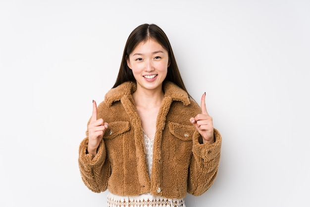 Young chinese woman posing in a white wall indicates with both fore fingers up showing a blank space.