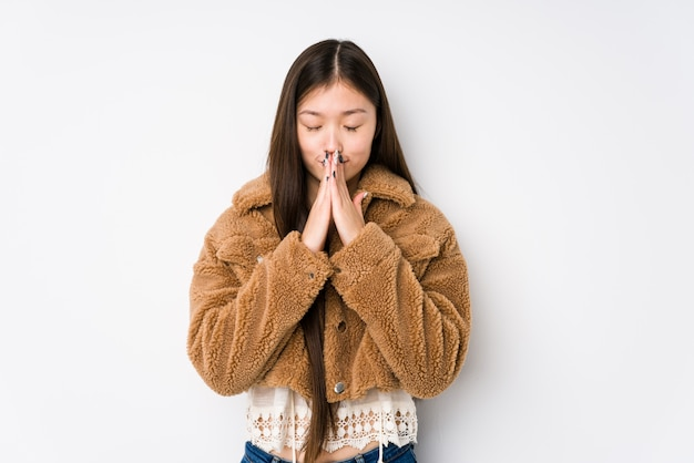 Young chinese woman posing in a white wall isolated holding hands in pray near mouth, feels confident.
